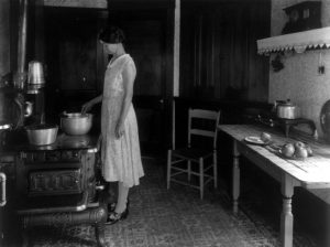 Farm woman cooking at stove in kitchen